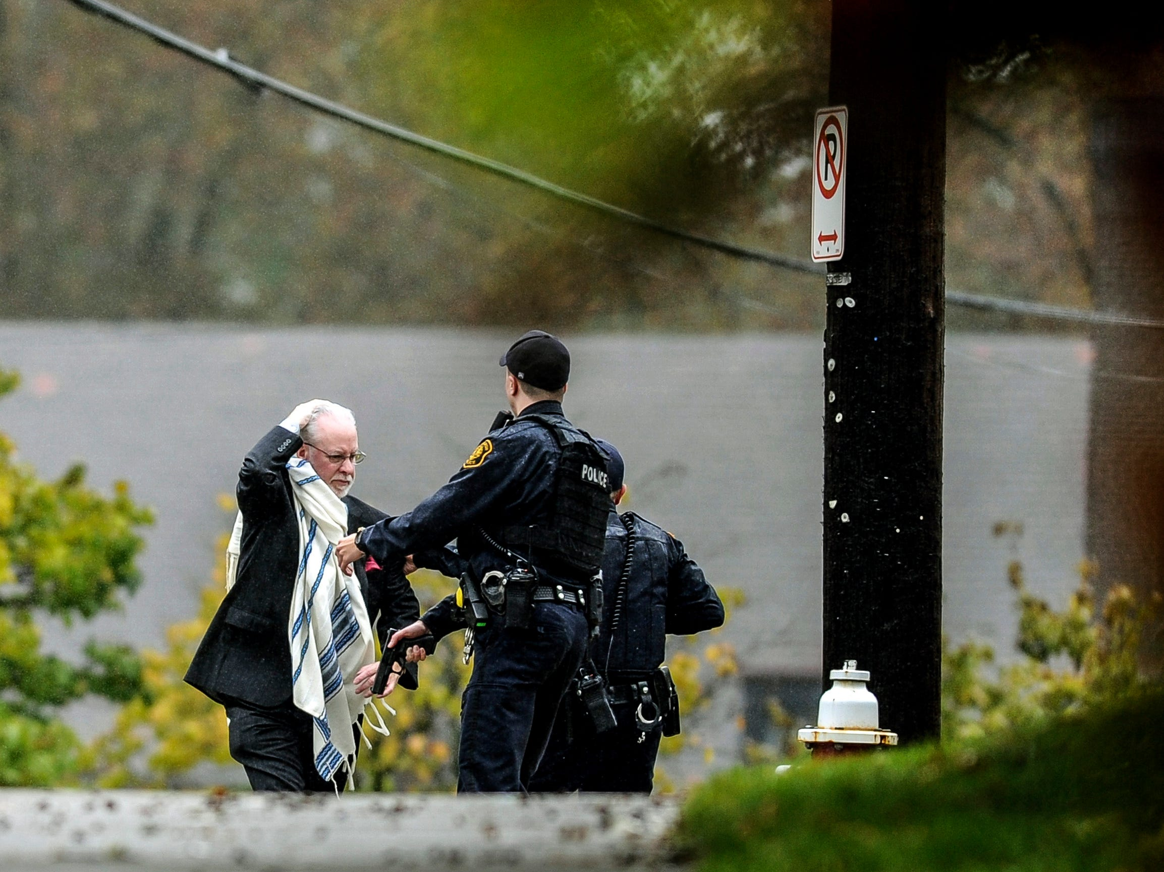 A man holds his head as he is escorted out of the Tree of Life Congregation by police following a shooting at the Pittsburg synagogue.