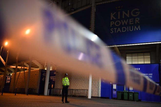 A police officer secures the area outside Leicester City FC's King Power Stadium after a helicopter crashed in a car park outside the stadium.