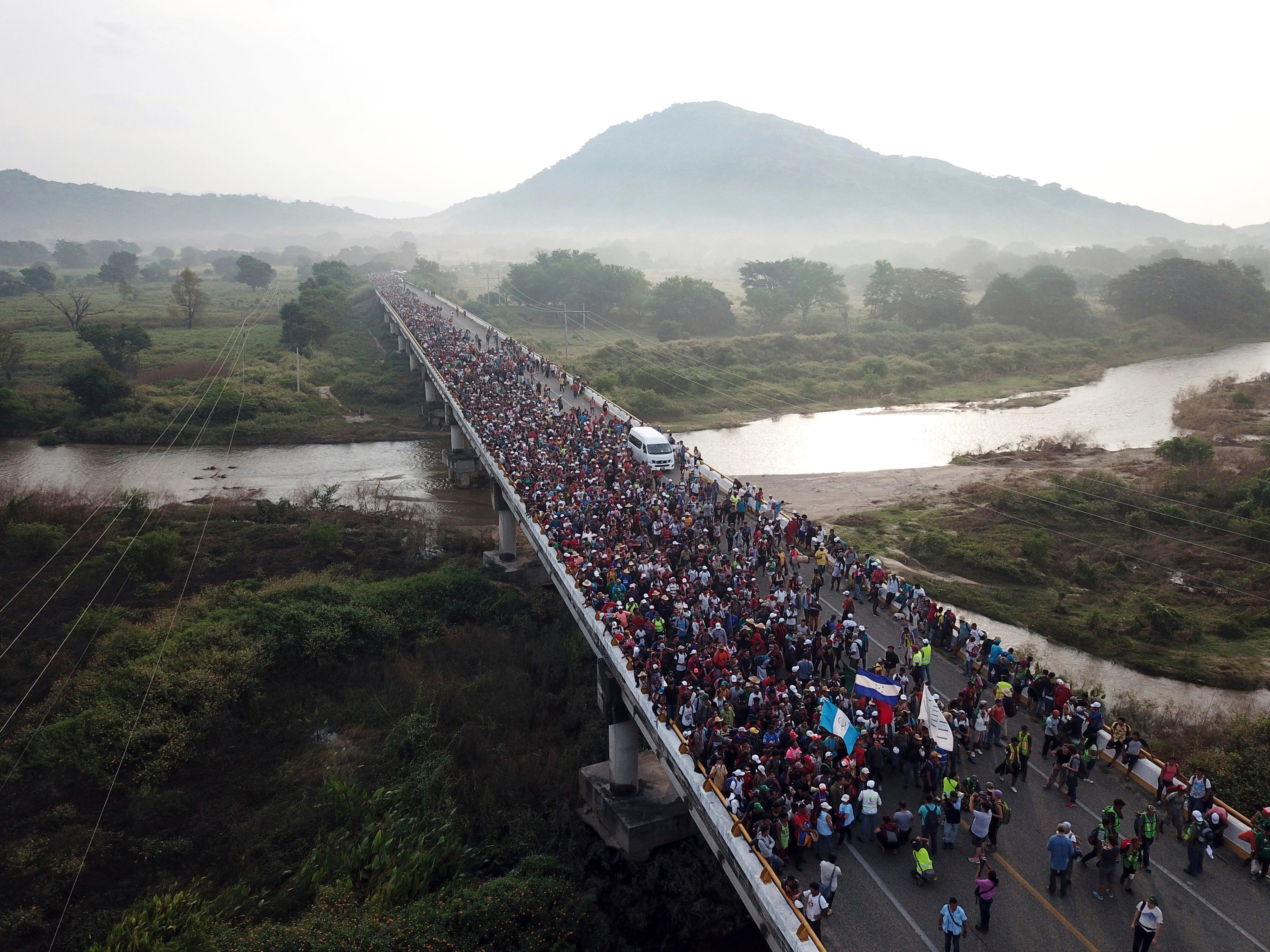 Members of a US-bound migrant caravan cross a bridge between the Mexican states of Chiapas and Oaxaca after federal police briefly blocked them outside the town of Arriaga on Oct. 27, 2018.