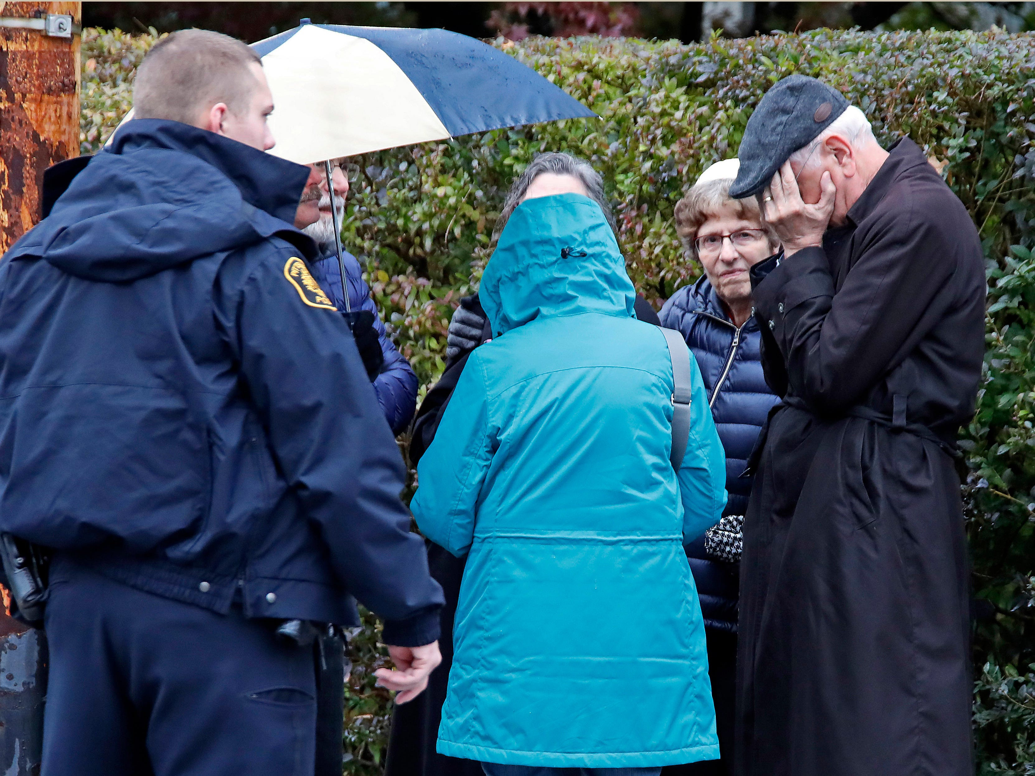 People gather on a corner near the Tree of Life Synagogue in Pittsburgh, Pa., where a shooter opened fire on Oct. 27, 2018, injuring multiple people.