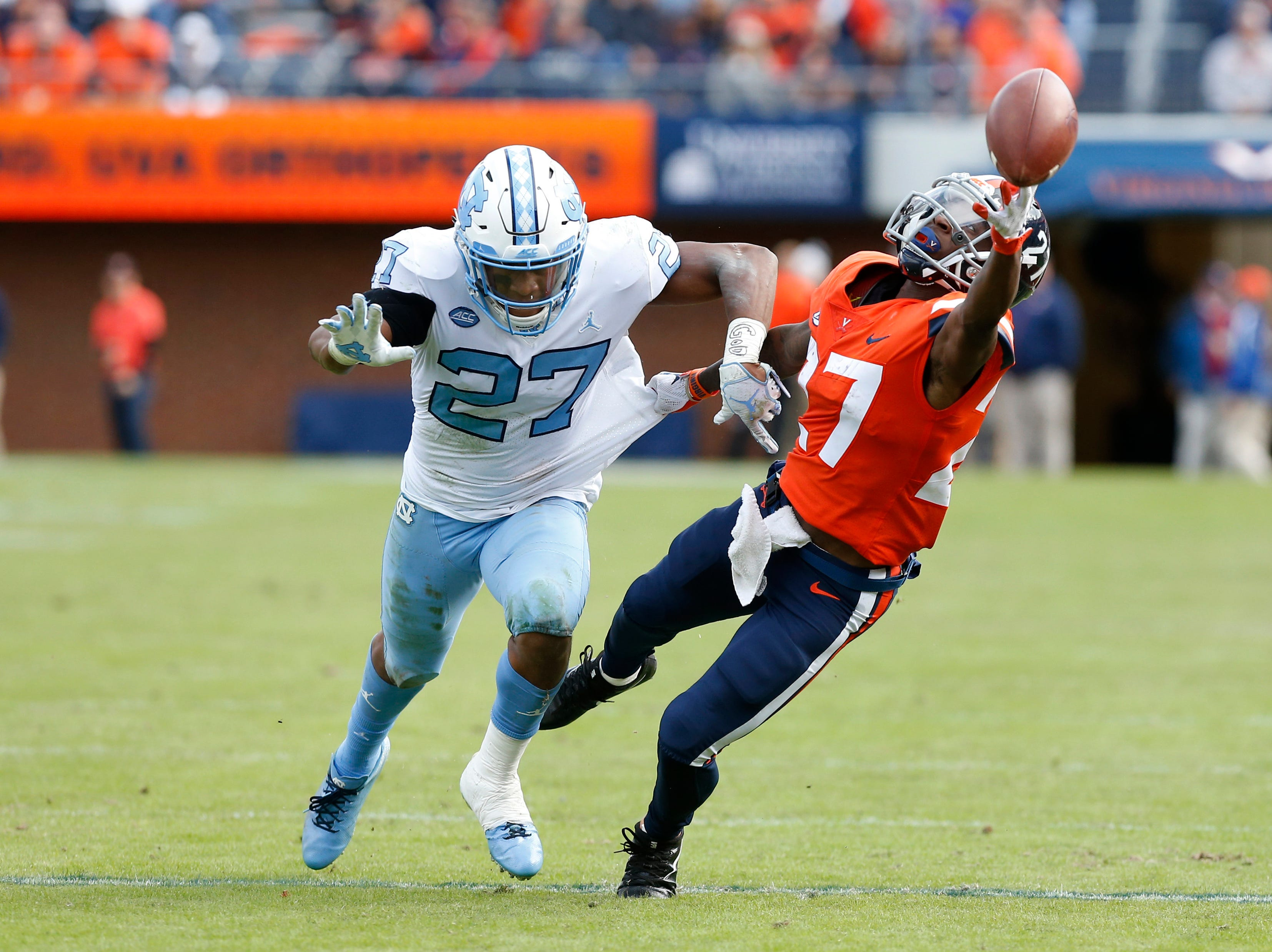 Virginia Cavaliers wide receiver Tavares Kelly (27) reaches for a pass intended for North Carolina Tar Heels running back Chavis Little (27) during the second half at Scott Stadium.