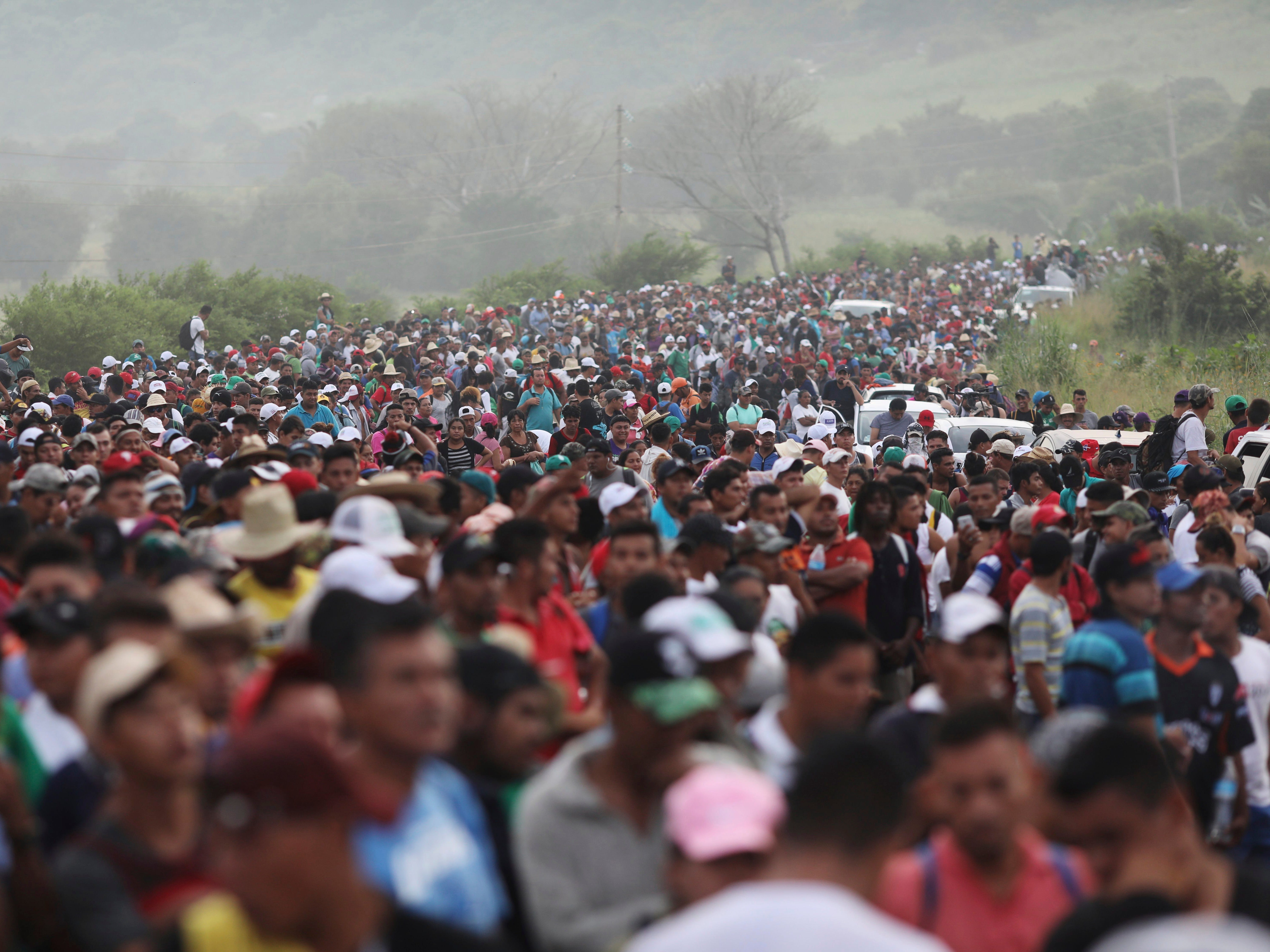 Members of a U.S.-bound migrant caravan stand on a road after federal police briefly blocked their way outside the town of Arriaga on Oct. 27, 2018. Hundreds of Mexican federal officers carrying plastic shields blocked the caravan from advancing toward the U.S. after several thousand of the migrants turned down the chance to apply for refugee status and obtain a Mexican offer of benefits.