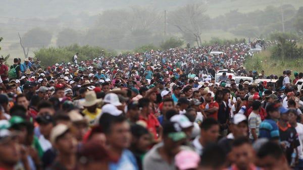 Members of a U.S.-bound migrant caravan stand on...