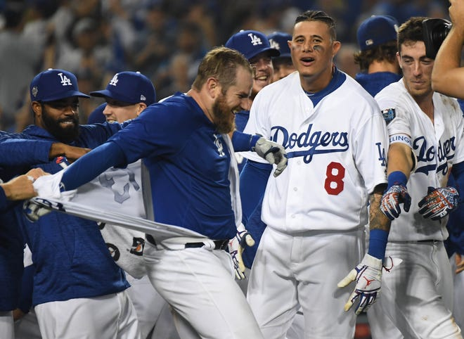 Max Muncy gets his jersey torn off by teammates after his walk-off home run in the 18th inning.