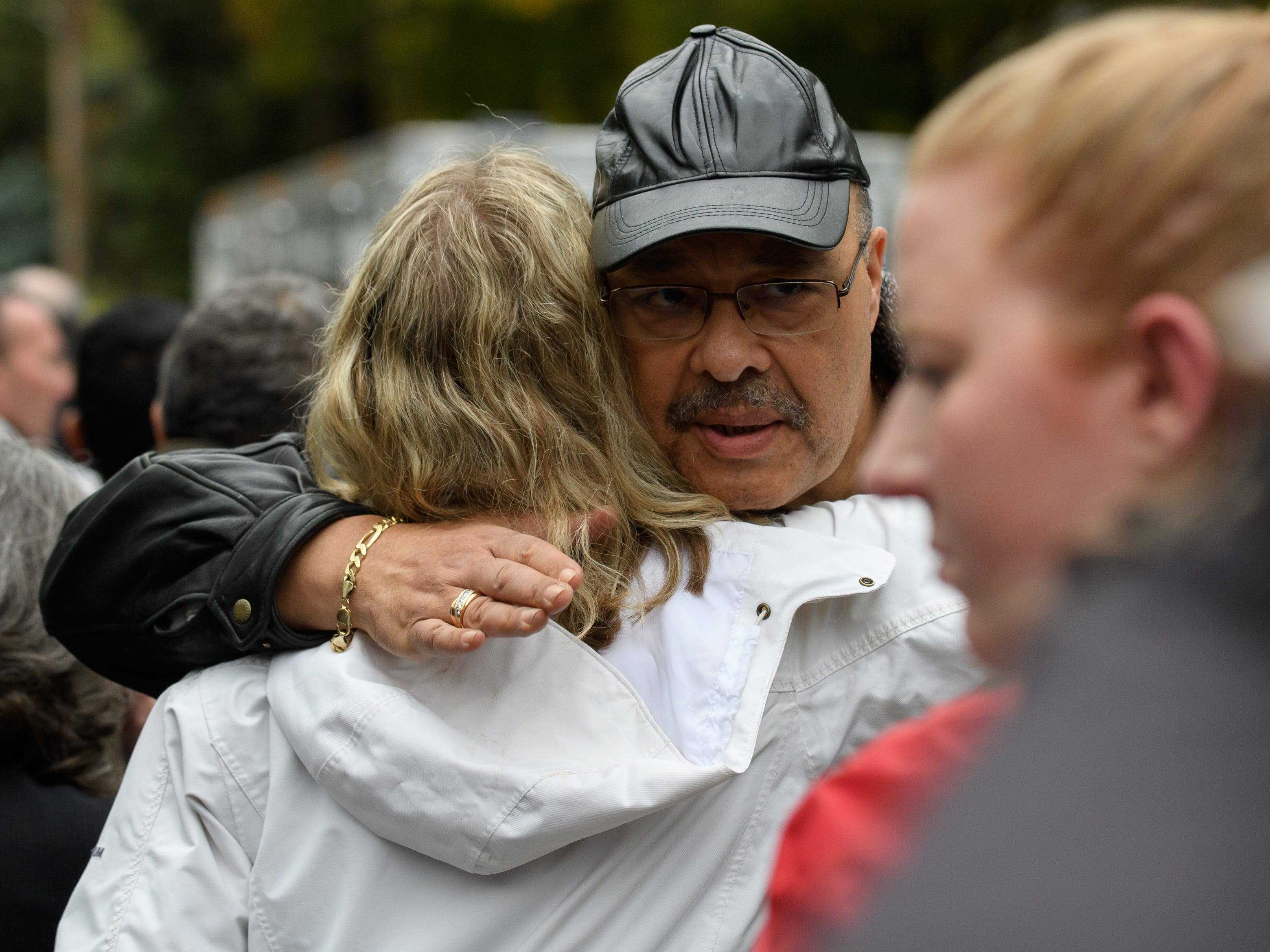 People comfort each other at the site of a mass shooting at the Tree of Life Synagogue.
