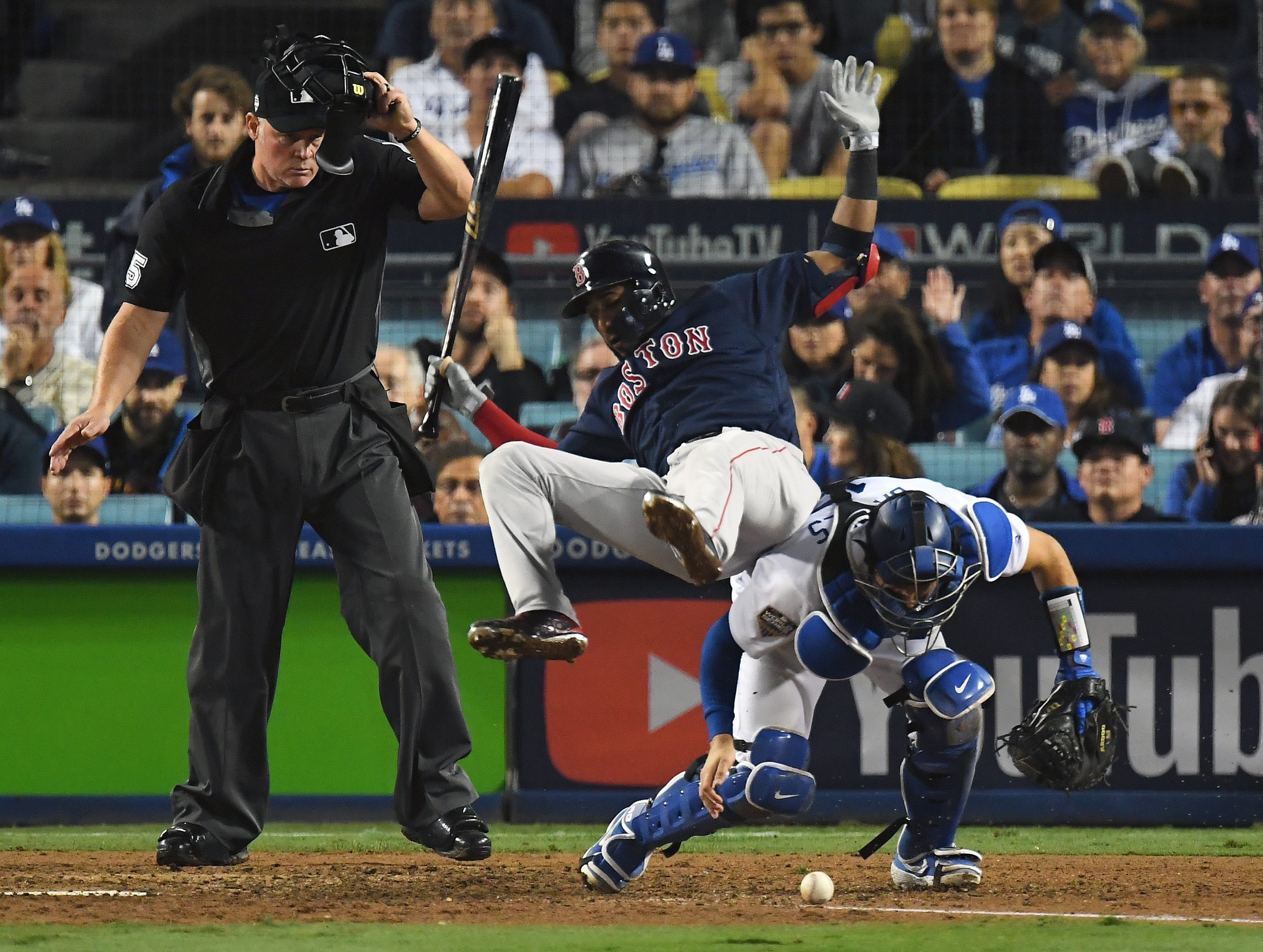 Game 3 at Dodger Stadium: Dodgers catcher Austin Barnes goes for a ball in the dirt as Eduardo Nunez tries to get out of the way in the 13th.