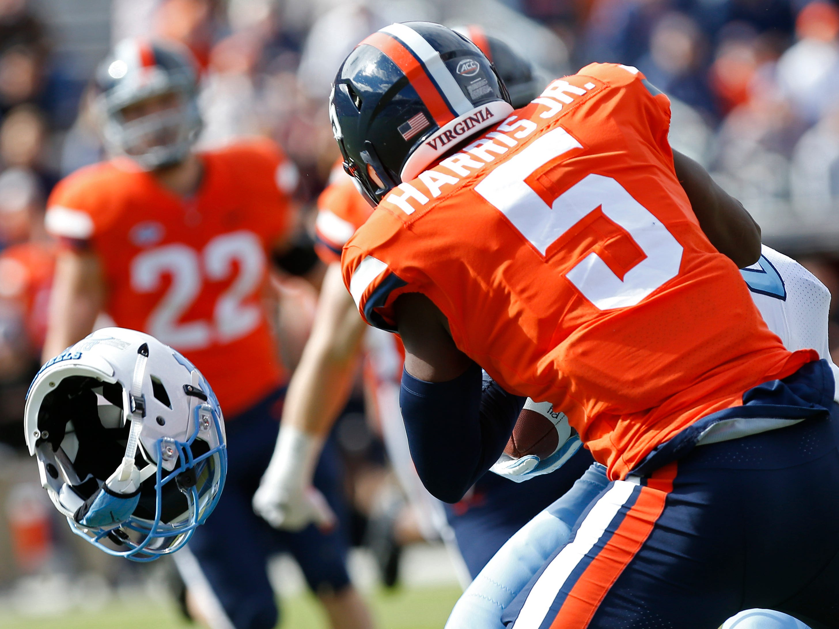 Virginia Cavaliers cornerback Tim Harris (5) tackles North Carolina Tar Heels tight end Carl Tucker (86) as his helmet falls off in the first quarter at Scott Stadium.