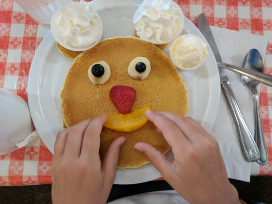 Iden Elliott adjusts a smiley face on pancakes at Ellen's Danish Pancake House in Buellton, California.