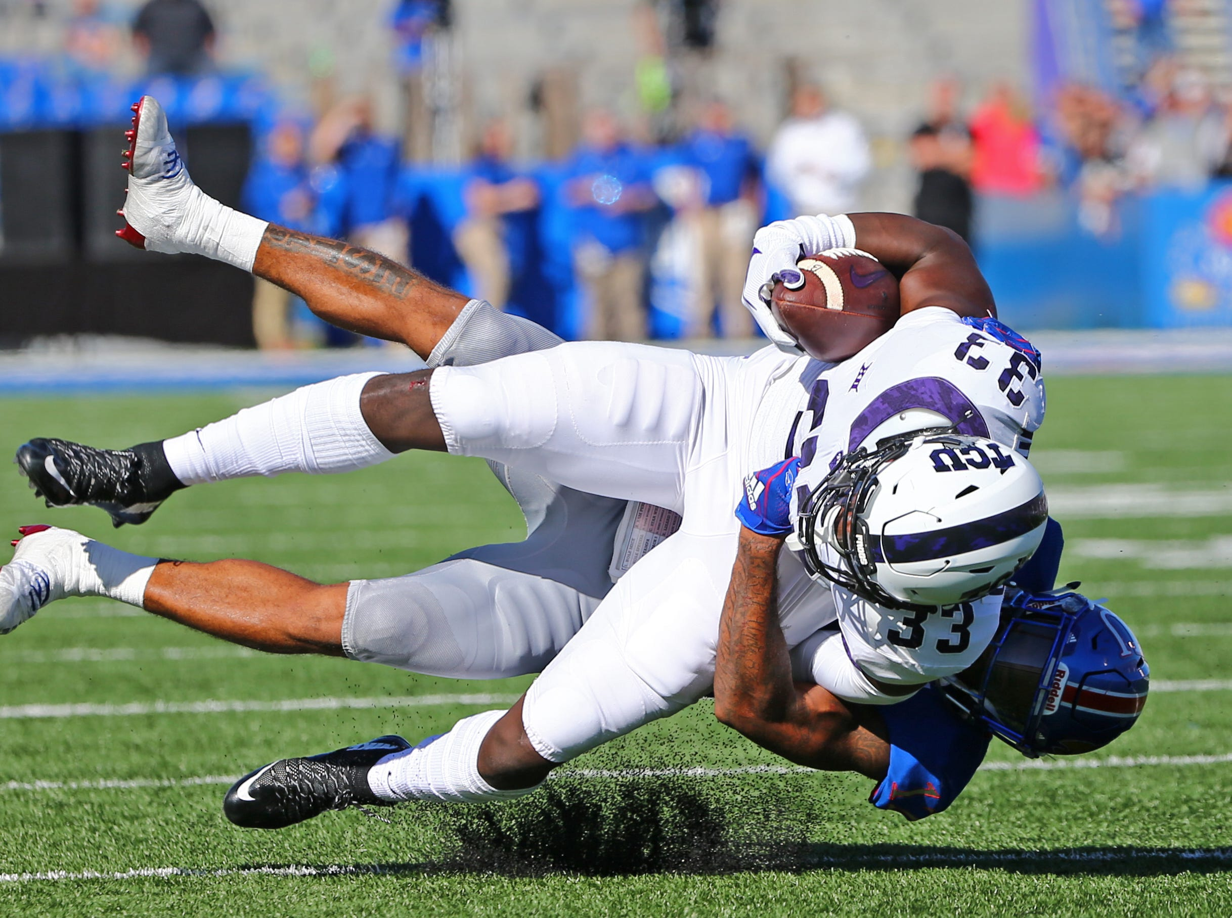 TCU Horned Frogs running back Sewo Olonilua (33) is tackled by Kansas Jayhawks safety Jeremiah McCullough (12) in the first half at Memorial Stadium.
