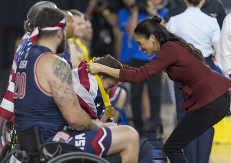 The Duchess of Sussex presents a medal during the medal presentation at the Invictus Games 2018.