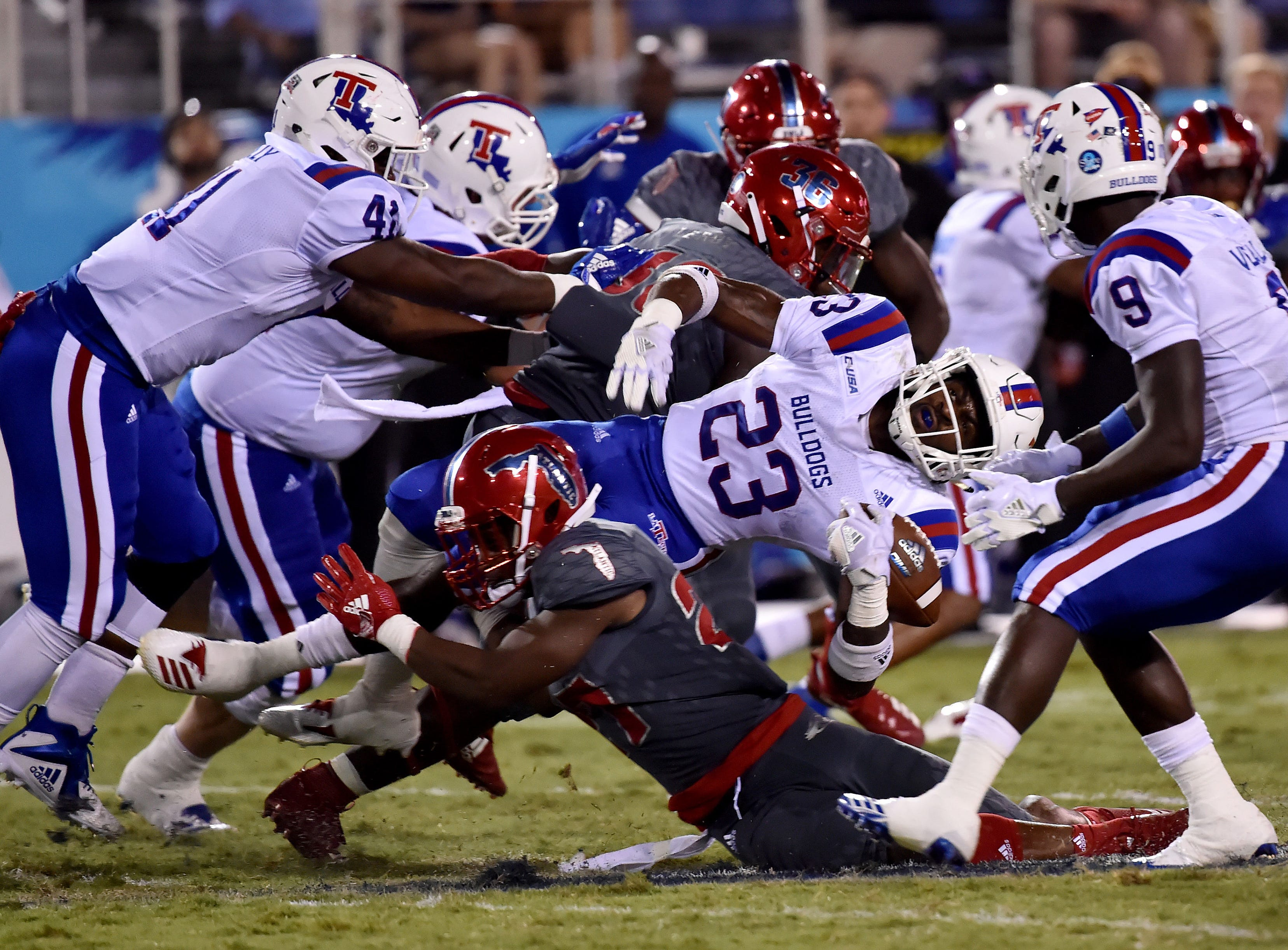 Florida Atlantic Owls safety Da'Von Brown (27) tackles Louisiana Tech Bulldogs running back Jaqwis Dancy (23) during the second half at FAU Football Stadium.