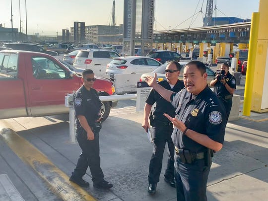 San Ysidro Port Director Sidney Aki (right) gestures toward the line of cars entering the U.S. from Mexico during a tour of the port on October 26, 2018, in San Diego, Calif.