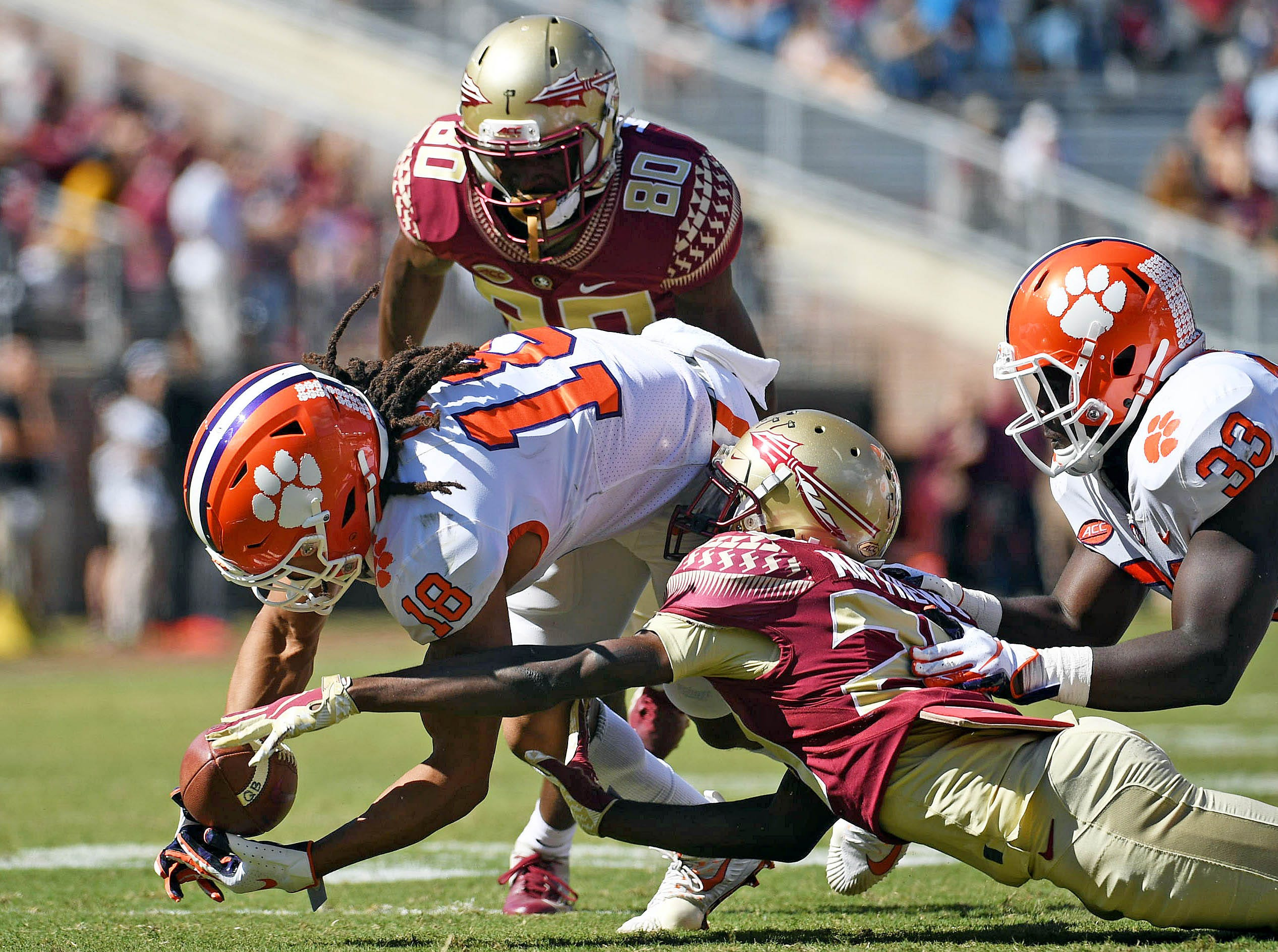 Clemson Tigers wide receiver TJ Chase (18) recovers a fumble on a punt by Florida State Seminoles wide receiver DJ Matthews (29) during the second half at Doak Campbell Stadium.