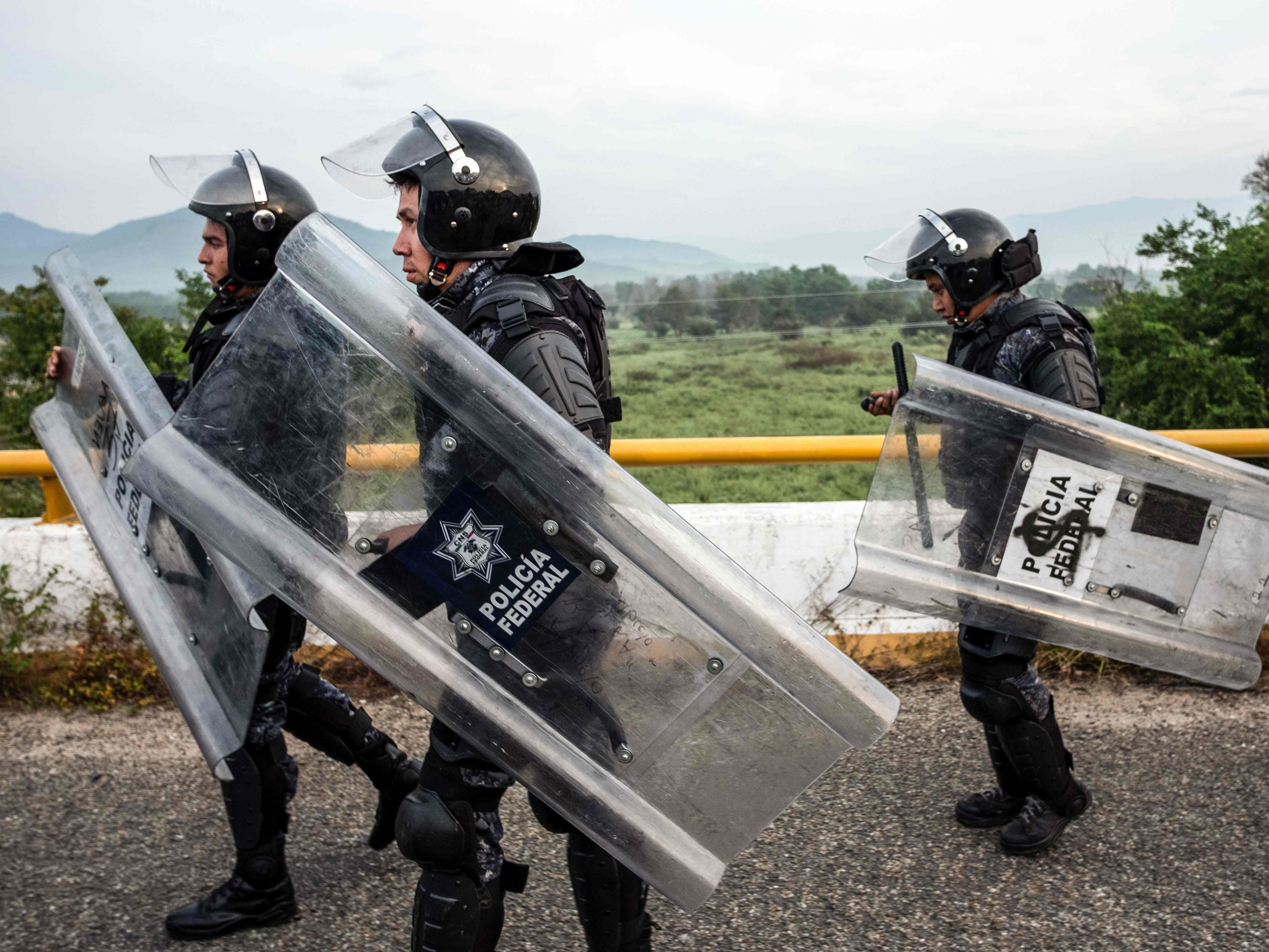 Mexican Federal Police officers allow the Honduran migrants to pass as they leave Arriaga on their way to San Pedro Tapanatepec, southern Mexico on Oct. 27, 2018.