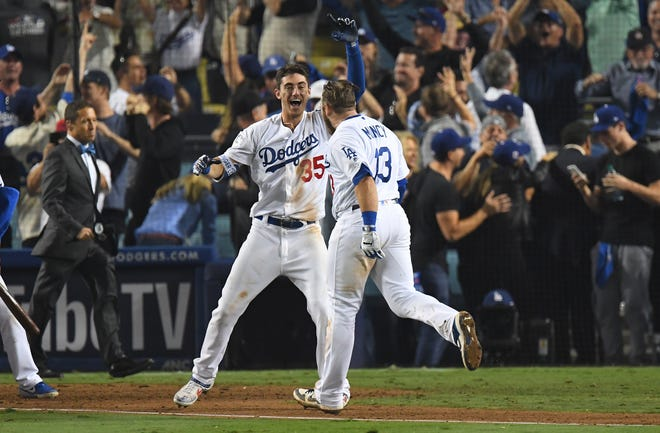 Los Angeles Dodgers first baseman Max Muncy celebrates with outfielder Cody Bellinger after hitting a solo home run to defeat the Boston Red Sox in the 18th inning in Game 3 of the 2018 World Series at Dodger Stadium.