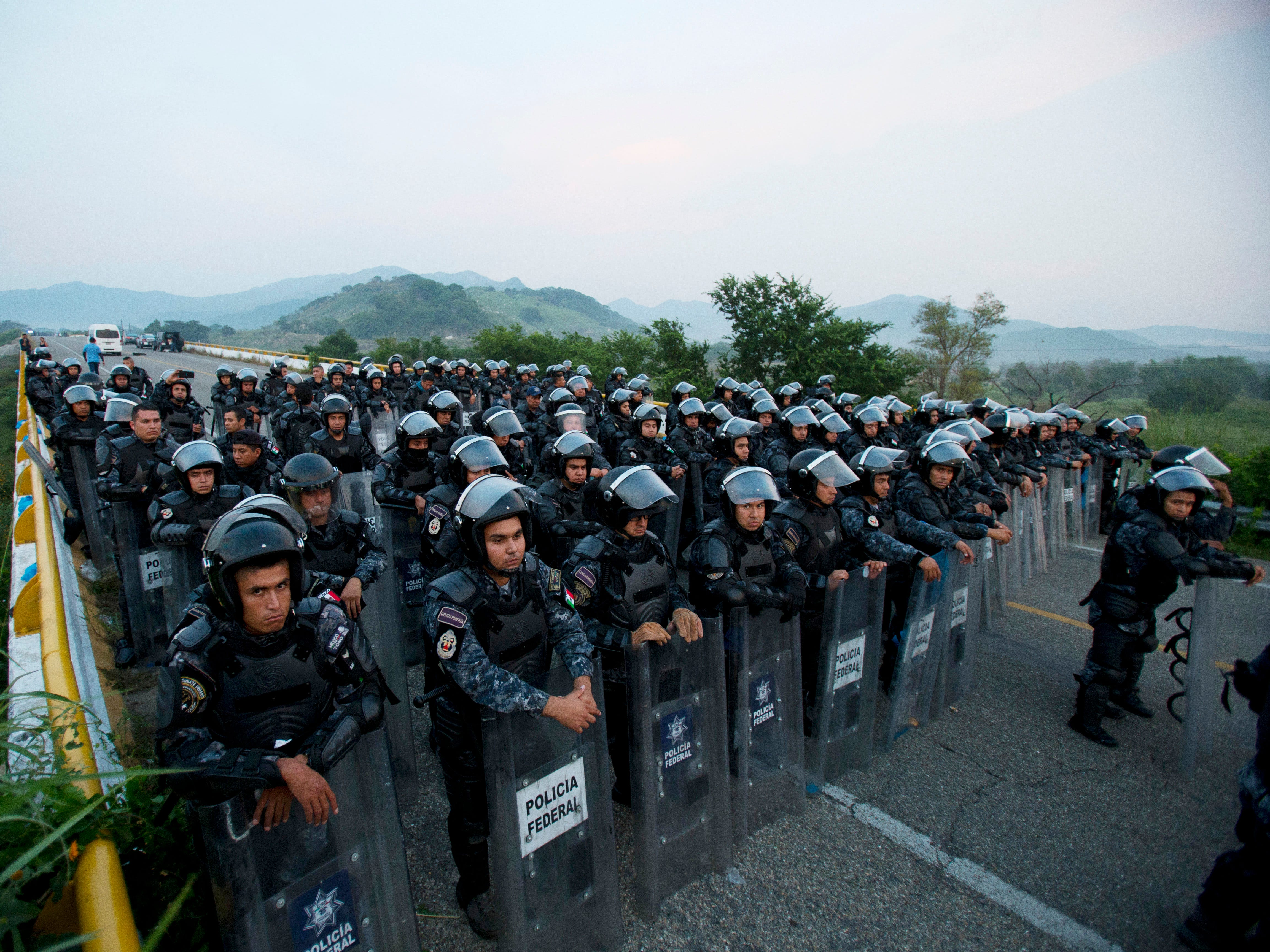 A wall of police in riot gear blocks the highway to stop a caravan of thousands of Central American migrants from advancing, outside Arriaga, Chiapas state, Mexico on Oct. 27, 2018. Eventually police let them pass, with the agreement that the dialogue with authorities would continue at their next stop.