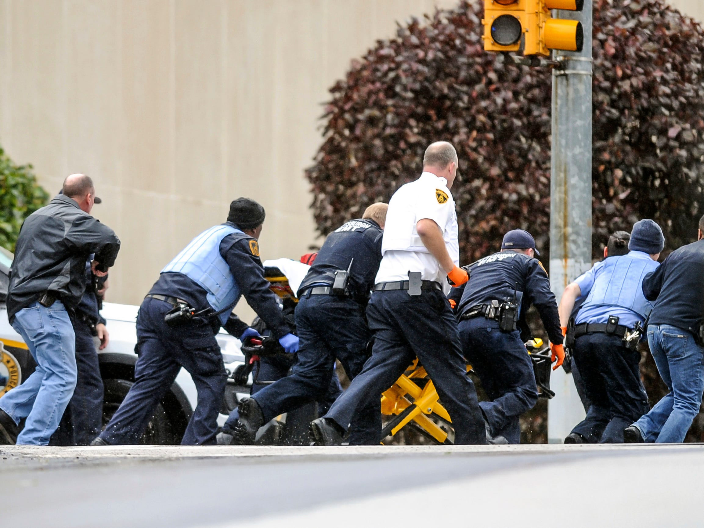 Law enforcement run with a person on a stretcher at the scene where multiple people were shot at the Tree of Life Congregation.