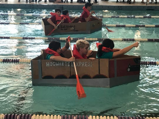 Neck and neck in the pool are a Google-themed team (top) and a Harry Potter-themed team during the third-annual Cardboard Boat Invitational held Saturday. The Google team of ATEMS High School students took top overall boat in the competition, while the Harry Potter boat lasted the longest of the five high school boats in the water.
