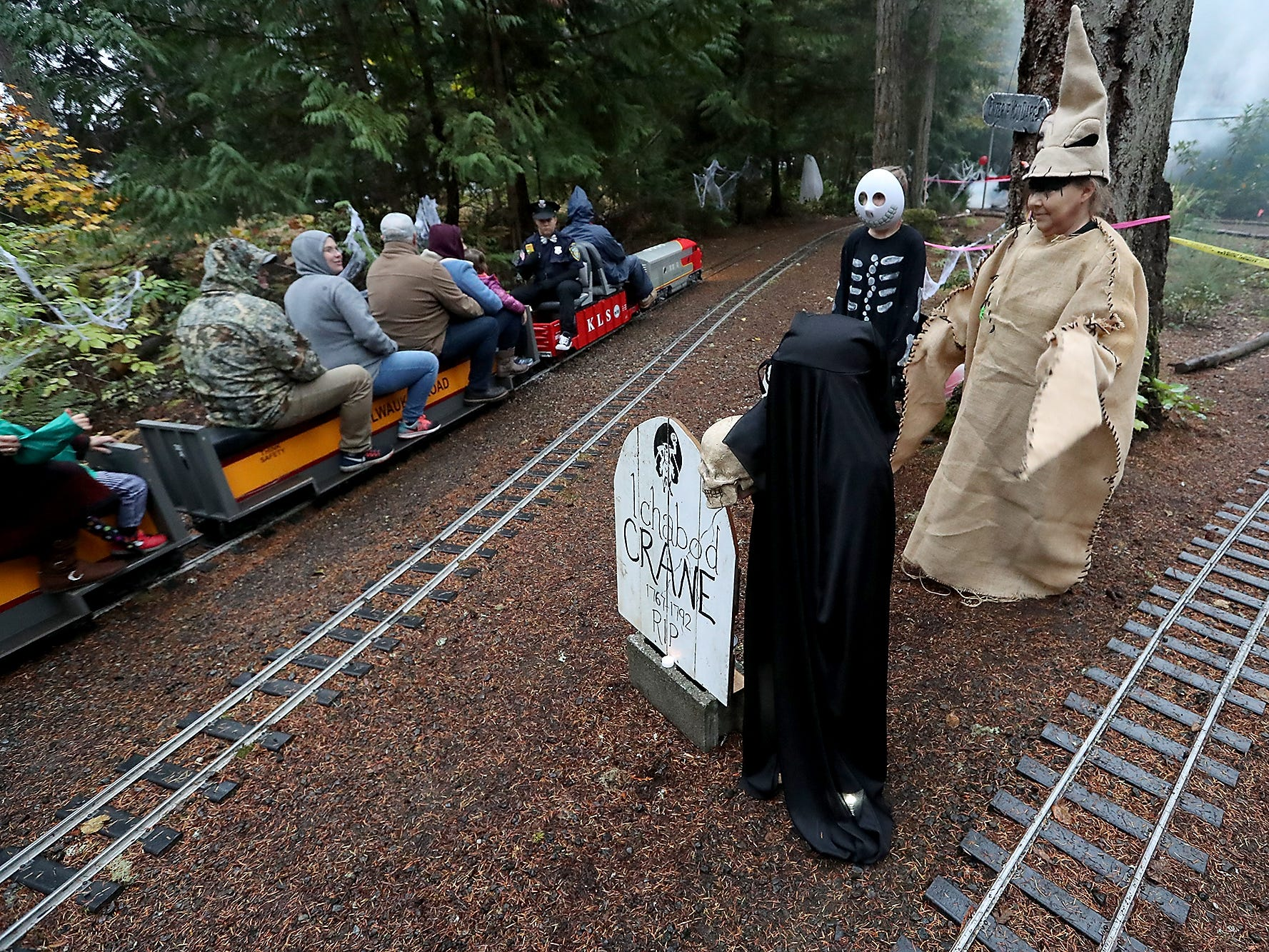 Dressed as characters from A Nightmare Before Christmas, members of the Burkhalter family (clockwise from front) Ryder, Ella, Katie and Annette stand among the headstones and train tracks as a Kitsap Live Steamers Ghost Train steams past on Saturday, October 27, 2018.