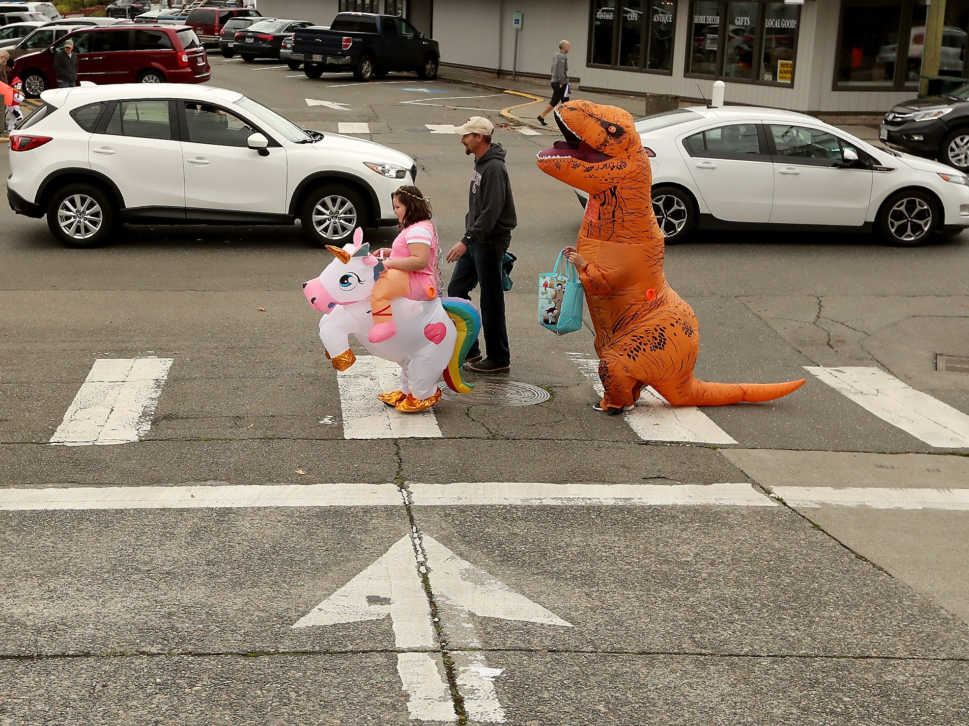Allison Siegrist, 9, leads the way with her unicorn as she, her father Josh and brother John, 11, (as a T-Rex) cross Frederick Ave while taking part in the Halloween Spookfest  in downtown Port Orchard on Saturday, October 27, 2018.