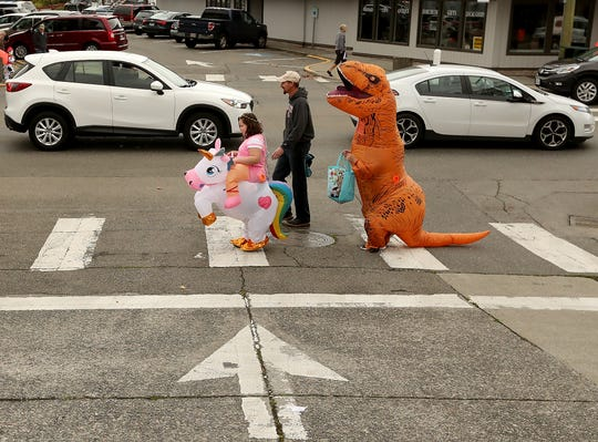 From left, Allison Siegrist, 9, her father Josh and her brother John cross Frederick Avenue in Port Orchard during Saturday's Spookfest trick-or-treating event. Allison was dressed as a unicorn and John as a tyrannosaurus rex.