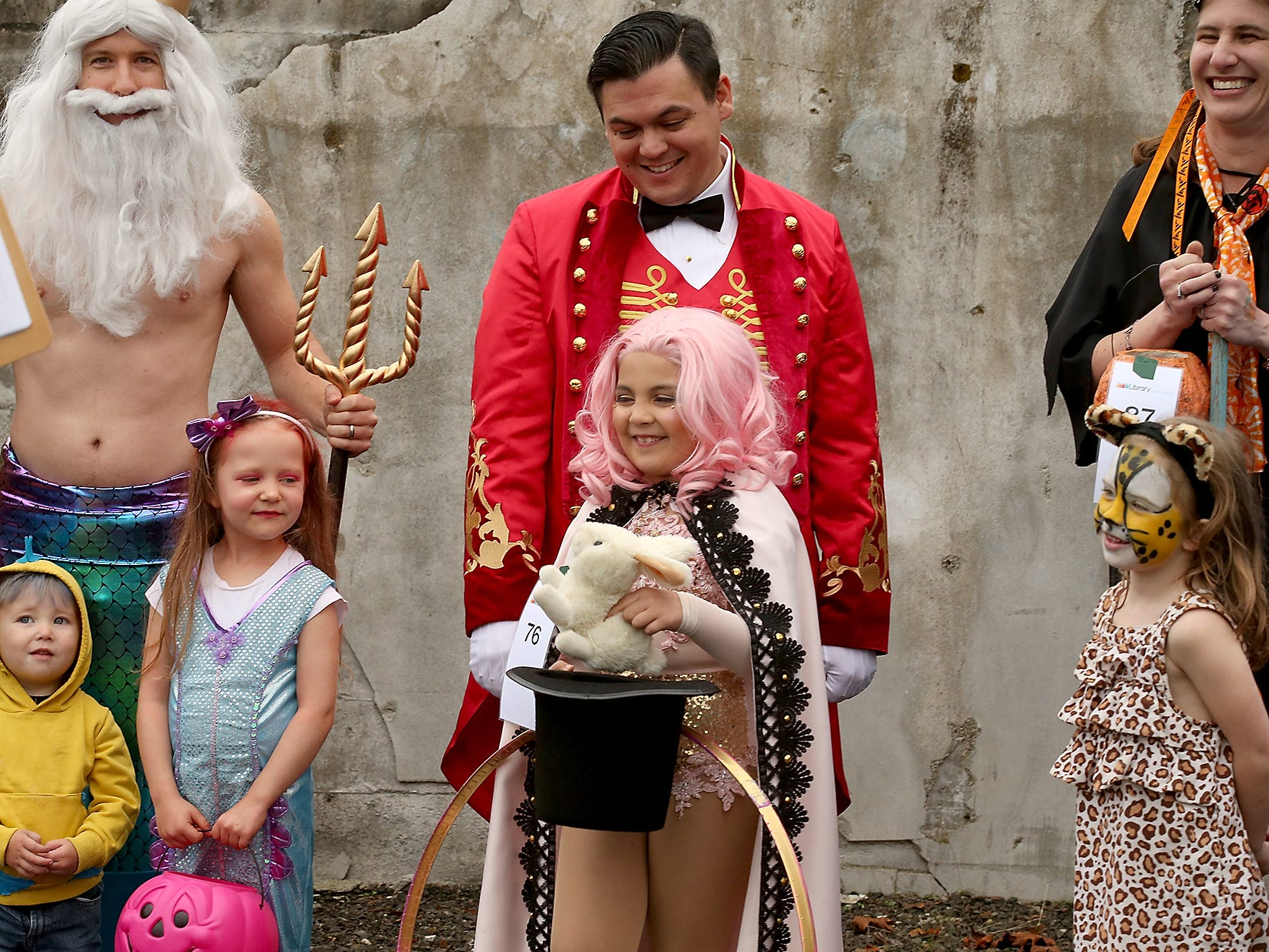 Demonstrating a trick for the judges while dressed as a circus performer, Dahlia Iguina, 6, (center) pulls a rabbit out her father Carlos's ringmaster hat during the costume judging at Spookfest in downtown Port Orchard on Saturday, October 27, 2018.