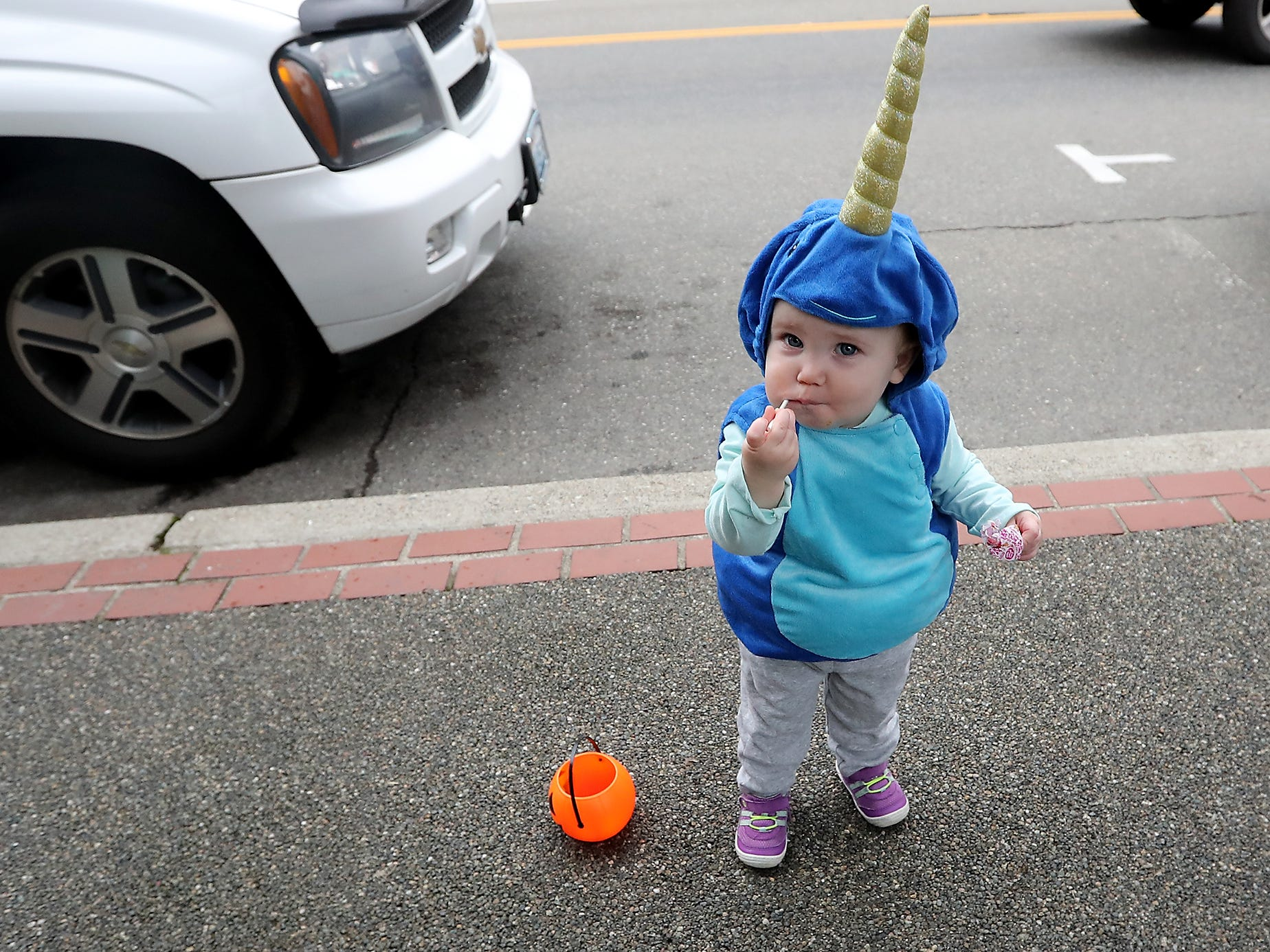 18-month-old Charlotte Hartford, pops a sucker into her mouth while dressed as a narwhal during the Halloween Spookfest in downtown Port Orchard on Saturday, October 27, 2018.