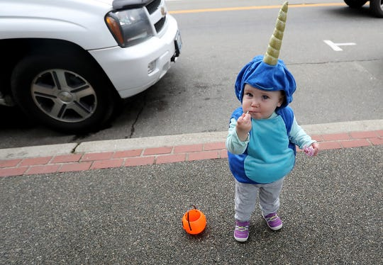 Charlotte Hartford, 18 months, samples some of the Halloween candy she received during the Port Orchard Spookfest event on Saturday in Port Orchard. She was dressed as a narwhal.