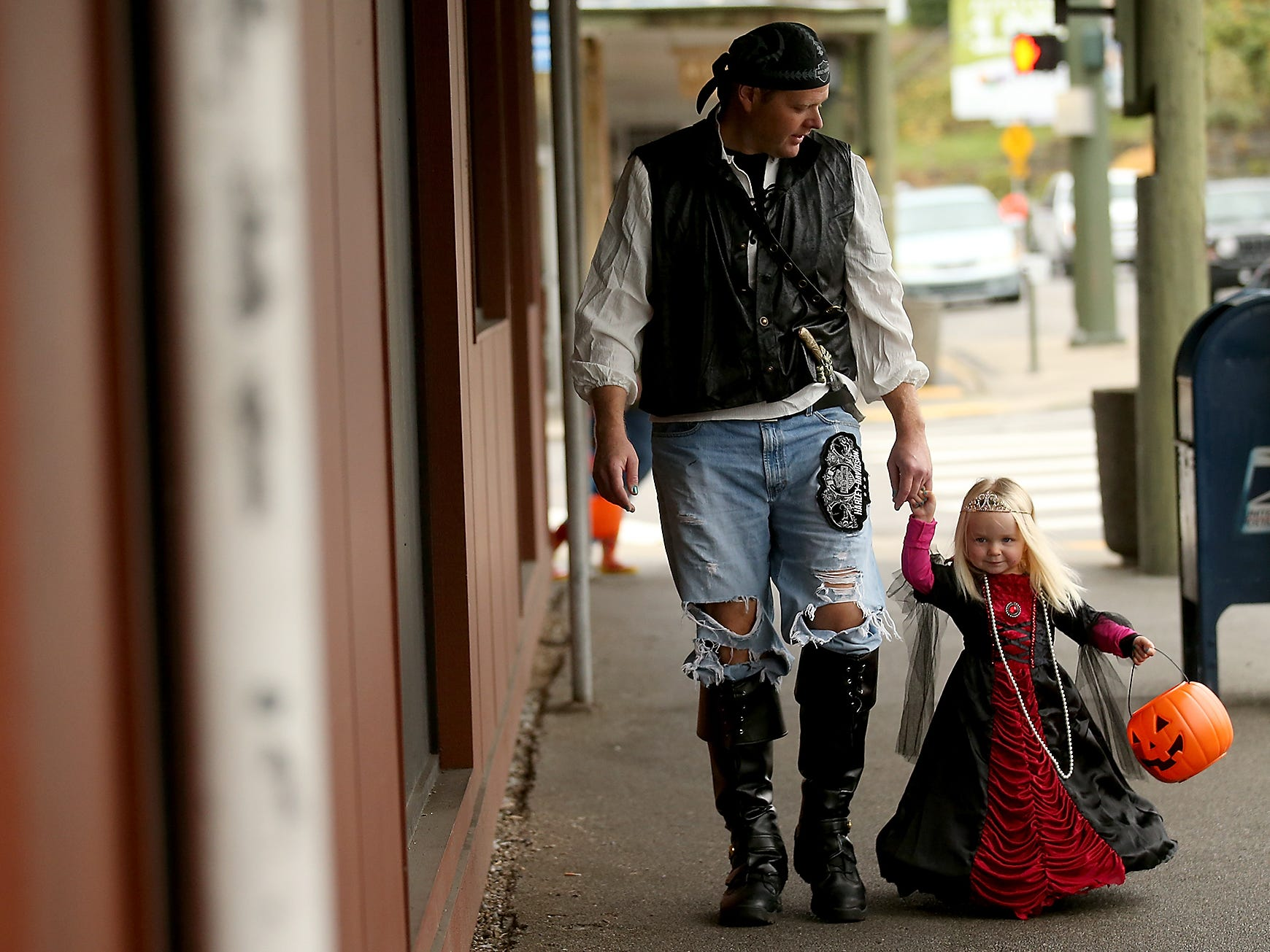 Brian Ottesen and daughter Danica, 3, make their way down the sidewalk in search of candy during the Halloween Spookfest in downtown Port Orchard on Saturday, October 27, 2018.