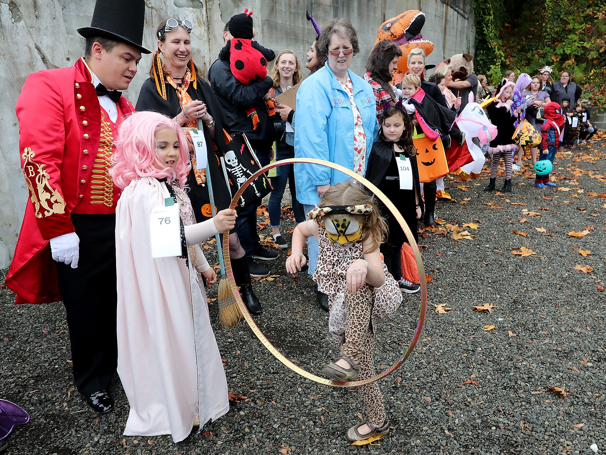 Dressed as a circus performer Dahlia Iguina, 6, holds out her hoop as Sasha Morris, 6, (dressed as a cheetah) jumps through it while the two perform the trick for the judges during the costume contest at Spookfest in downtown Port Orchard on Saturday, October 27, 2018. The two came up with the trick as they were standing next to each other in line for judging.