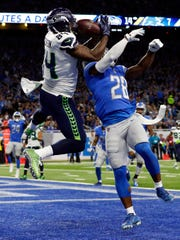 Seattle Seahawks tight end Ed Dickson (left) hauls in a 12-yard scoring pass from Russell Wilson after getting behind Detroit defender Quandre Diggs (28).