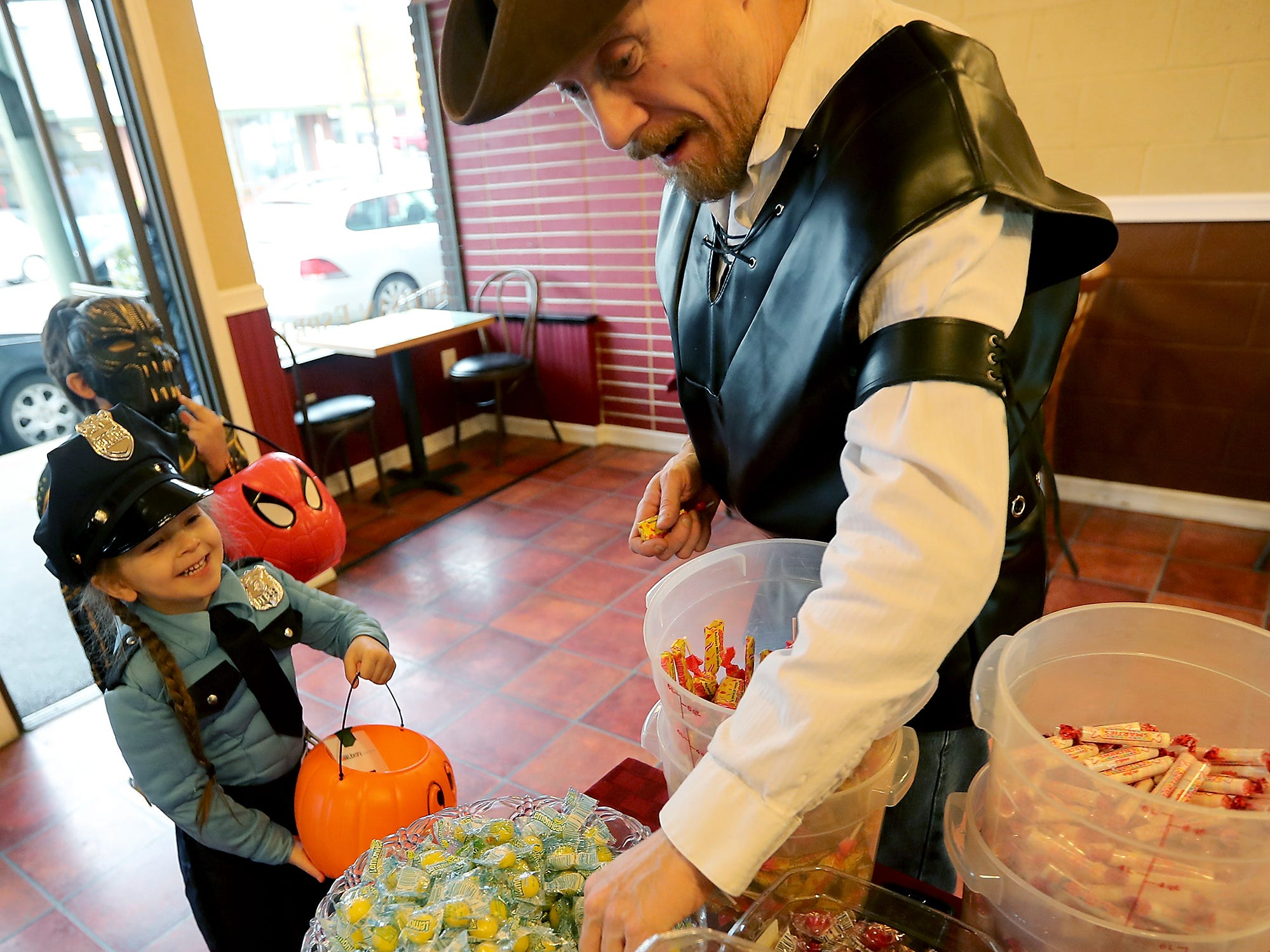 Eva Berger, 4, is all smiles in her police officer costume as John Strasinger, of Carter And Company, grabs her a piece of every different kind of candy that he has during the Halloween Spookfest trick-or-treating in downtown Port Orchard on Saturday, October 27, 2018.