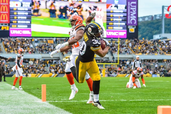 Pittsburgh Steelers running back James Conner (30) runs for a touchdown as Cleveland Browns defensive end Myles Garrett (95) goes for the tackle during the third quarter at Heinz Field in 2019. Whether playing in Three Rivers Stadium or at Heinz Field, most of Cleveland's trips down the Turnpike and across the Pennsylvania state line have not gone well. The Browns are just 6-41 on their visits to the Steel City since 1970.