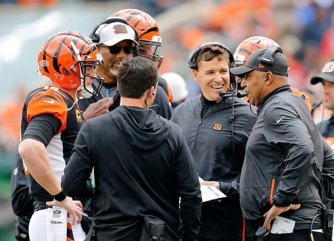 Cincinnati Bengals quarterback Andy Dalton (14) confers with head coach Marvin Lewis and offensive coordinator Bill Lazor during a time out in the second quarter of the NFL Week 8 game between the Cincinnati Bengals and the Tampa Bay Buccaneers at Paul Brown Stadium in downtown Cincinnati on Tuesday, Oct. 16, 2018.
