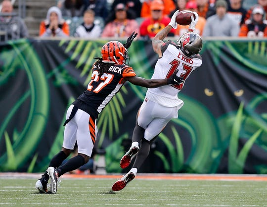Tampa Bay Buccaneers wide receiver Mike Evans (13) catches a deep pass under pressure from Cincinnati Bengals cornerback Dre Kirkpatrick (27) in the second quarter of the NFL Week 8 game between the Cincinnati Bengals and the Tampa Bay Buccaneers at Paul Brown Stadium in downtown Cincinnati on Tuesday, Oct. 16, 2018.