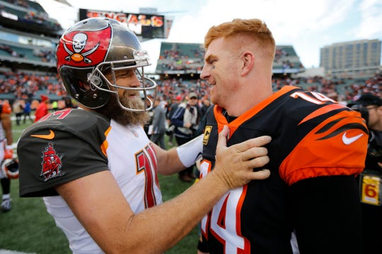 Tampa Bay Buccaneers quarterback Ryan Fitzpatrick (14) and Cincinnati Bengals quarterback Andy Dalton (14) hug after the fourth quarter of the NFL Week 8 game between the Cincinnati Bengals and the Tampa Bay Buccaneers at Paul Brown Stadium in downtown Cincinnati on Tuesday, Oct. 16, 2018. The Bengals won 37-34 on a last second field goal.
