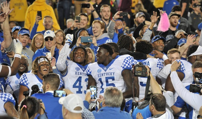 Kentucky Wildcats players celebrate with fans in the stands after defeating the  the Missouri Tigers at Memorial Stadium/Faurot Field.