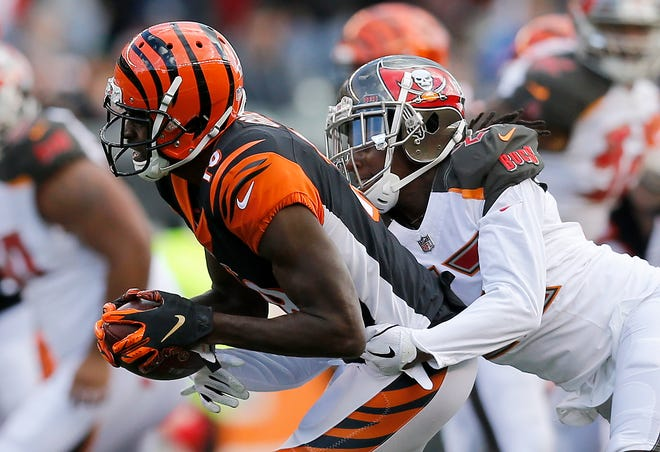 Cincinnati Bengals wide receiver A.J. Green (18) holds on to a catch as he's brought down by Tampa Bay Buccaneers free safety Chris Conte (23) in the fourth quarter of the NFL Week 8 game between the Cincinnati Bengals and the Tampa Bay Buccaneers at Paul Brown Stadium in downtown Cincinnati on Tuesday, Oct. 16, 2018. The Bengals won 37-34 on a last second field goal.
