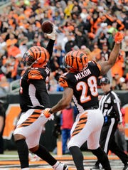 Cincinnati Bengals offensive tackle Bobby Hart (68) and running back Joe Mixon (28) celebrate after Mixon's touchdown in the first quarter of the NFL Week 8 game between the Cincinnati Bengals and the Tampa Bay Buccaneers at Paul Brown Stadium in downtown Cincinnati on Tuesday, Oct. 16, 2018.
