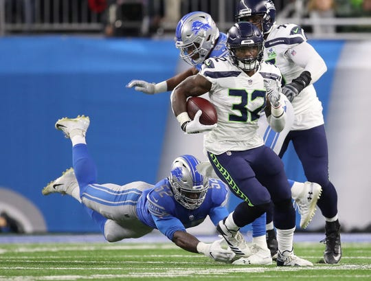 Chris Carson of the Seattle Seahawks runs for yardage past a diving Christian Jones of the Detroit Lions at Ford Field on Oct. 28, 2018 in Detroit.