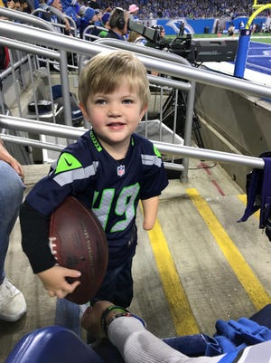 Blake Venier, 3, of Gibraltar attended Sunday's Detroit Lions game against Seattle Seahawks at Ford Field.  Venier was born without his left hand.