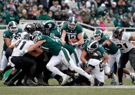 Michigan State quarterback Rocky Lombardi emerges from the pile on a quarterback sneak for a first down against Purdue during the fourth quarter Saturday, Oct. 27, 2018, in East Lansing.