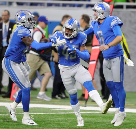 Tracy Walker, left, Charles Washington, center and Sam Martin celebrate a play against the Seahawks on Oct. 28.