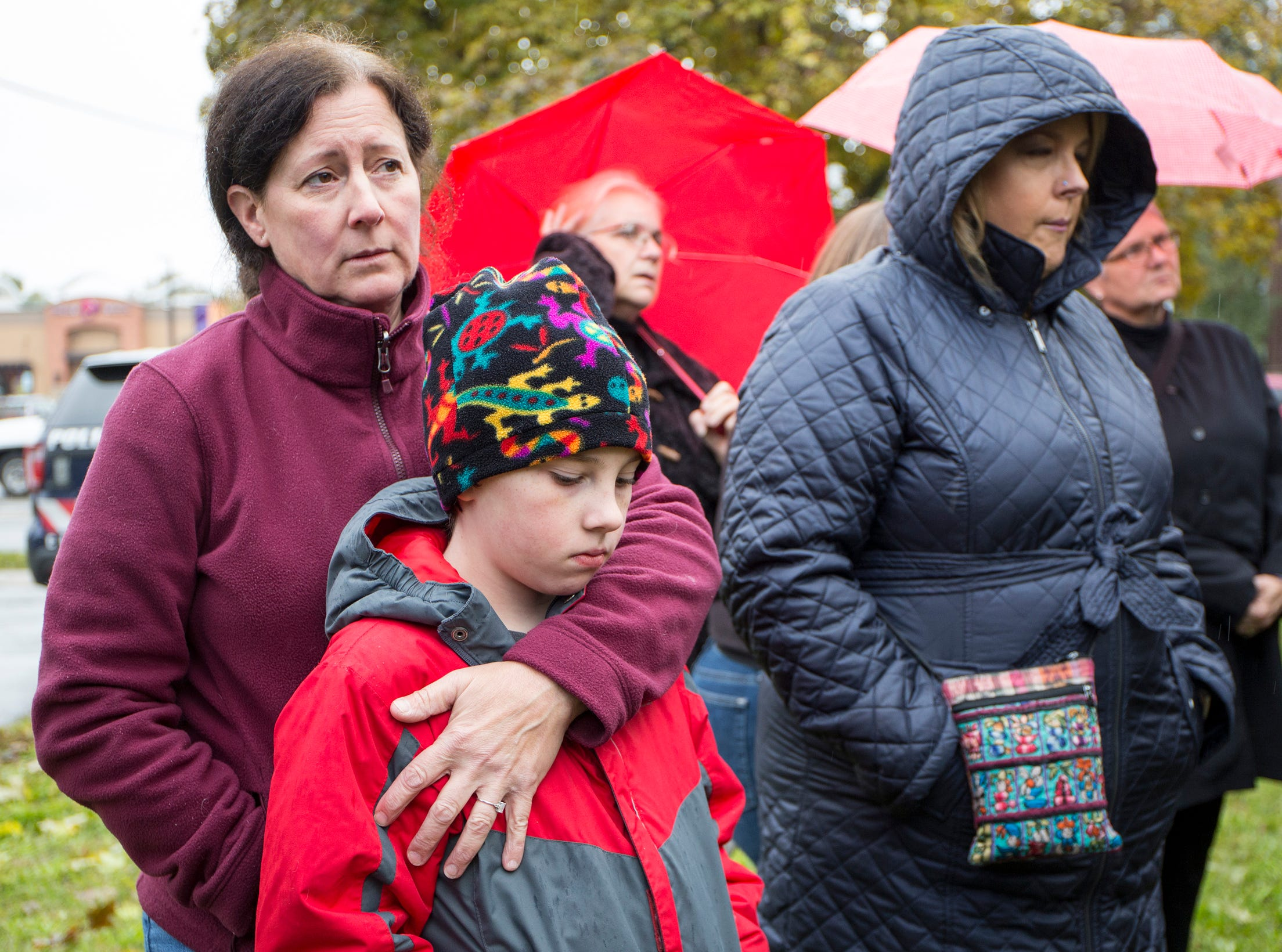 From left, Liz Schiffer, 55 and her son Michael Trombley, 10 of Ferndale, gather with others during a vigil, in honor of 11 people who were killed during a mass shooting in Pittsburgh, at Jewish Ferndale in Ferndale, Mich., Sunday, Oct. 28, 2018.