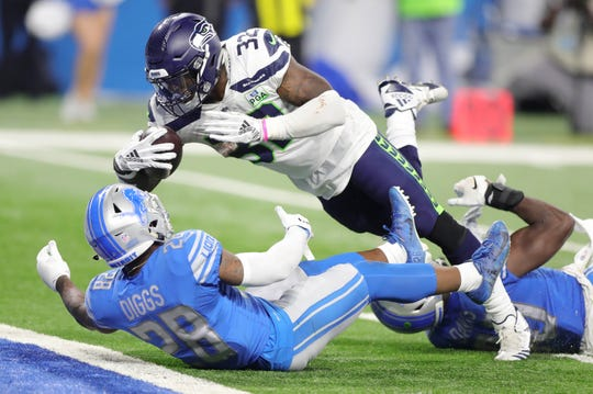 Detroit Lions' Quandre Diggs (28) and Jarrad Davis (40) give up a touchdown to Seattle Seahawks running back Chris Carson during the fourth quarter Sunday, October 28, 2018 at Ford Field in Detroit.