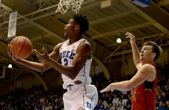 Duke's Cam Reddish (2) goes in for a shot as Ferris State's Cole Walker (34) defends in the first half of an NCAA college basketball exhibition game, Saturday, Oct. 27, 2018, in Durham, N.C.