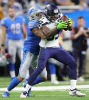 Detroit Lions defensive back Teez Tabor tackles Seattle Seahawks receiver David Moore during the first half Sunday, October 28, 2018 at Ford Field in Detroit.