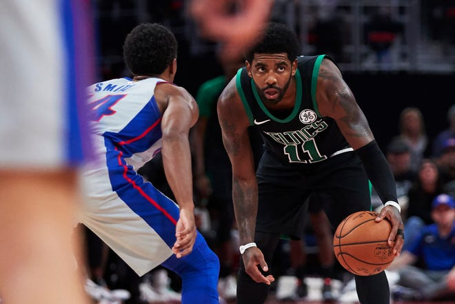 Celtics guard Kyrie Irving is defended by Pistons guard Ish Smith in the first half at Little Caesars Arena on Saturday.