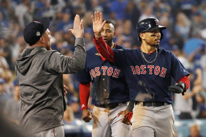 Mookie Betts of the Boston Red Sox celebrates with a teammate at the dugout entrance after Betts scored on a three-run RBI double by Steve Pearce in the ninth inning.