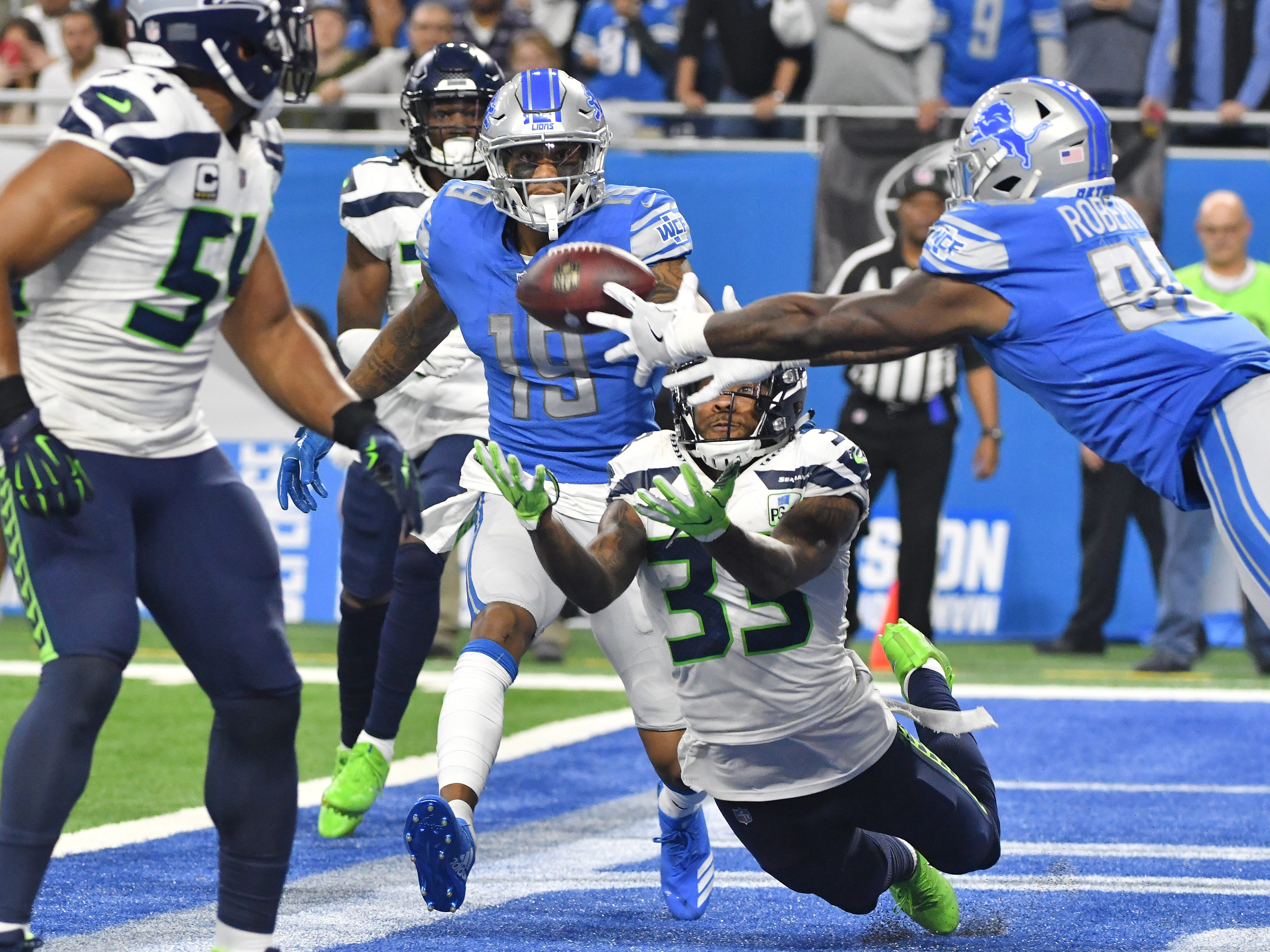 Lions' Kenny Golladay and Michael Roberts battle for a ball thrown into the end zone with Seahawks' Cedric Thompson, with no one able to pull it in late in the fourth quarter.